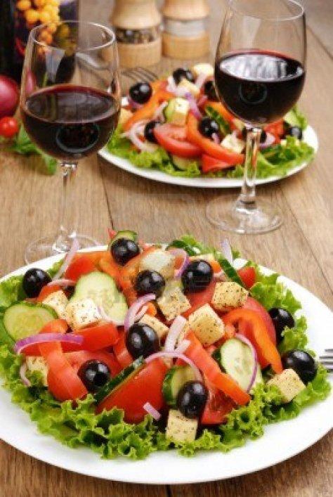 12896326-ensalada-de-vegetales-y-un-vaso-de-vino-tinto-en-la-mesa-de-roble
